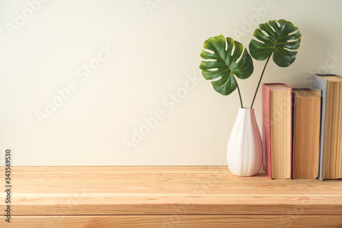Obraz Books and plant on wooden table with copy space. Education background - fototapety do salonu