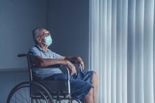 Aged Man Wearing Face Mask Sitting In A Wheel Chair Alone
