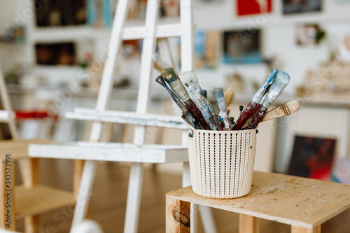 Photo Old brushes for painting,smeared with colored paint, are in the artist's studio