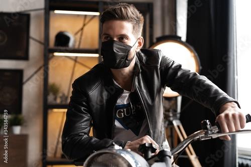Handsome brutal male biker in black mask in leather jacket sitting on motorcycle looking forward Fotobehang
