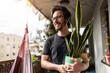Leinwandbild Motiv Young man taking care of his plants on a balcony