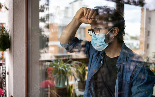 Obraz Man with face mask looking out of window  - fototapety do salonu