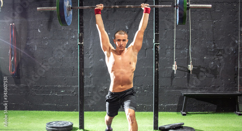 Photo Active young fit shirtless sportsman doing lifting weights in the gym