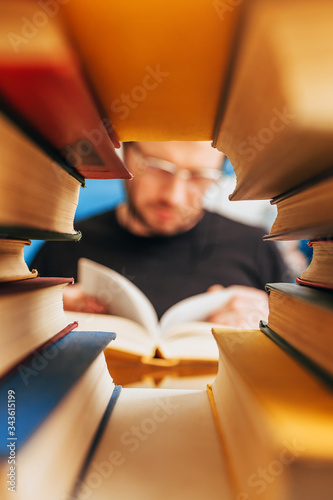 An avid reader with a book in defocus in a frame of books - the concept of liter Canvas Print