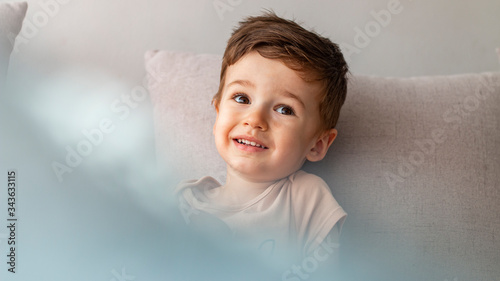 Fototapeta Portrait of happy joyful beautiful little boy. Close up portrait of an excited little boy laughing on gray background. Happy little boy at home. Bright closeup portrait of adorable happy toddler obraz