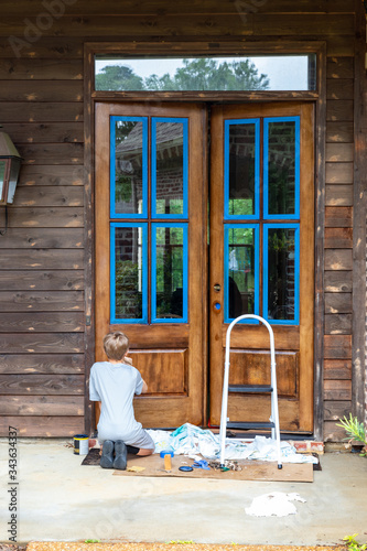 Person applies stain while refinishing wooden front door to house Wall mural