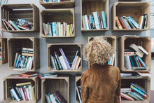 Rear View Of Woman Standing Against Book Shelves In Library