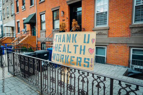 Fotografia Hoboken, NJ - April 27 2020: A sign in the street in front of a brownstone that