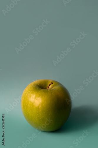 Photo an apple on an aquamarine background