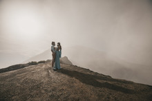 Couple In Protective Masks Hug. Man Is Holding The Golf Club And Stads With His Woman Who Is Wearing A Blue Dress. They Stand On The Crater Of The Volcano With Views Of The Mountains, Hills And Clouds
