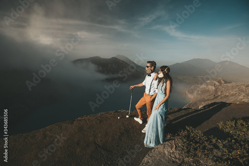 Couple in protective masks stand on the crater of the volcano with views of the mountains, hills and clouds Billede på lærred