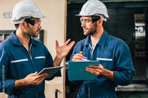 Engineer teamwork cooperate with worker to checking factory machine for safety and talking together Canvas Print