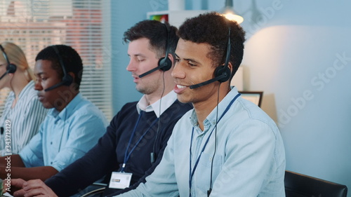 Obraz Medium shot of black call center agent feeling exhausted and broken-down after telephone call with the client. He working with mixed-race team in modern office. - fototapety do salonu
