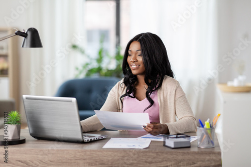 Obraz remote job, technology and people concept - happy smiling african american young woman with laptop computer and papers working at home office - fototapety do salonu