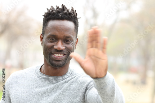 Valokuvatapetti Happy black man waving hand looking camera