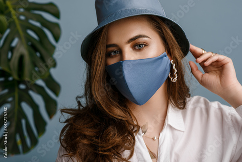 Fototapeta Woman wearing stylish outfit with luxury designer protective blue face mask, bucket hat, pearl earrings