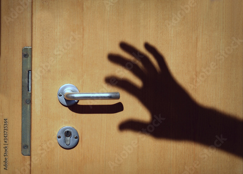 Shadow of a hand moving towards a doorhandle Fototapeta