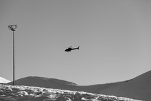 Helicopter In Clear Sky And Snowy Ski Slope