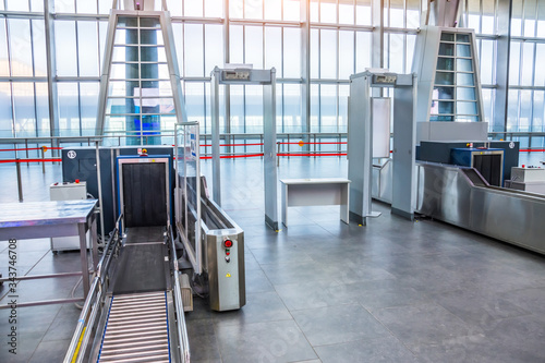 Obraz X-ray machine for screening passenger luggage with frame metal detector at the airport check-in counter. - fototapety do salonu
