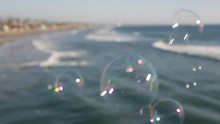Blowing Soap Bubbles On Ocean Pier In California, Blurred Summertime Background. Creative Romantic Metaphor, Concept Of Dreaming Happiness And Magic. Abstract Symbol Of Childhood, Fantasy, Freedom.