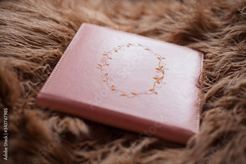 Valokuva A pink photobook in a leather cover lies on brown fur