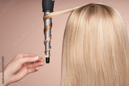 The hairdresser curls long hair with a Curling iron. Beautiful woman with long straight hair. Smooth hairstyle