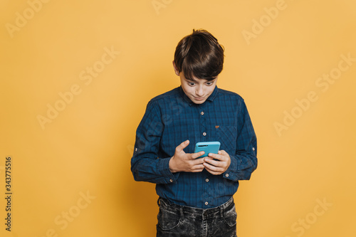 Photo Cute boy in casual shirt and jeans stare ate his smartphone with extremely wide open eyes, shocked by received message, standing over yellow backdrop