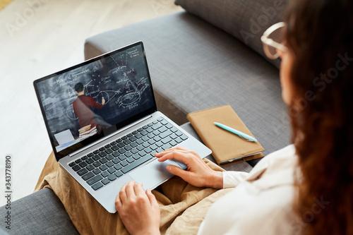 Fototapeta Unrecognizable woman sitting on sofa at home watching online conference video, horizontal high angle shot obraz na płótnie