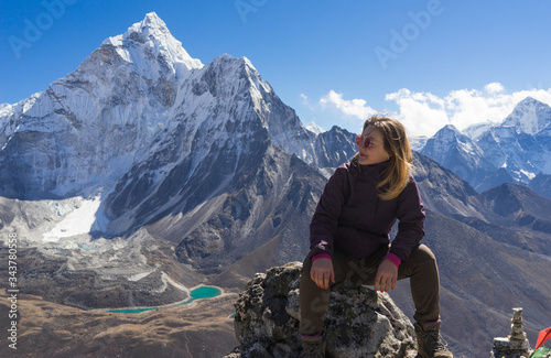 Photo A young female caucasian trekking in front of Ama Dablam having a rest after the