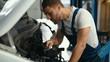 Auto mechanic working with engine in garage. Repair service.