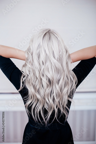 Carta da parati Female back with silver grey ash blonde curly wavy long hair in black dress