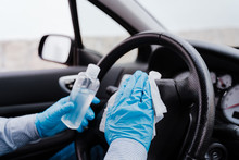 Unrecognizable Man In A Car Using Alcohol Gel To Disinfect Steering Wheel During Pandemic Coronavirus Covid-19