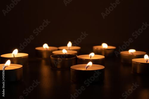 Religious and devoutness scene: candles burning in the dark Fototapeta