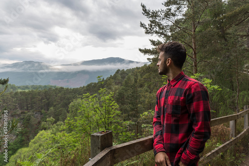 dark-haired man in a plaid shirt in a viewpoint of a national park Tablou Canvas
