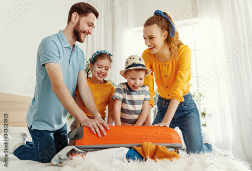 Excited family packing baggage on bed anticipating trip Canvas Print