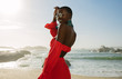 canvas print picture - Beautiful african woman in red dress enjoying on the beach