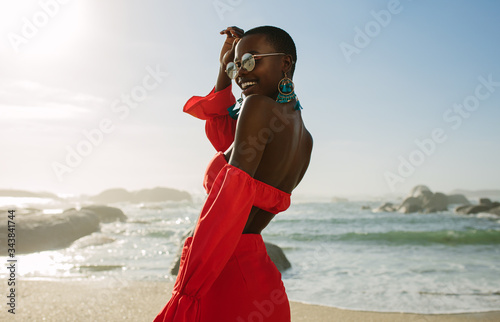 Beautiful african woman in red dress enjoying on the beach