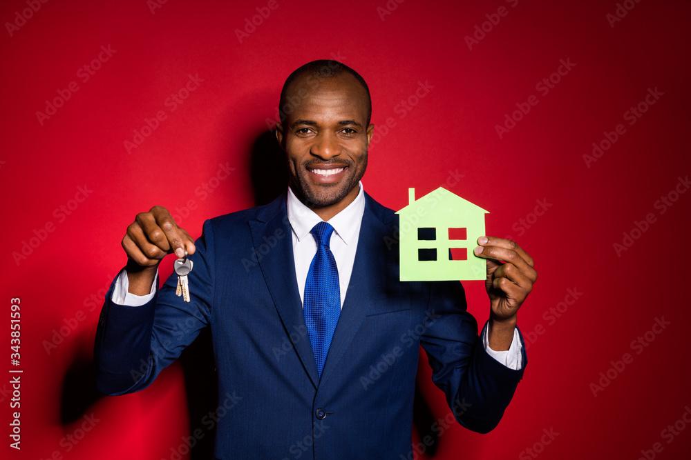 Fototapeta Photo of handsome dark skin business guy hold key chain green paper house real estate agent broker offer sale price wear blue formalwear suit tuxedo isolated red burgundy background