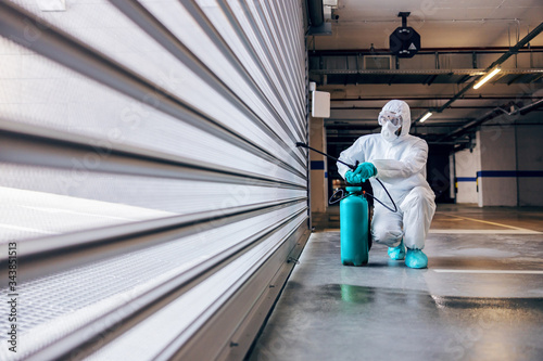 Papel de parede Worker in sterile protective suit and mask crouching sterilizing door of a garage from corona virus / covid-19