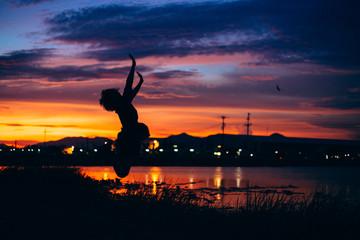 practicing yoga at beach, under sunset.