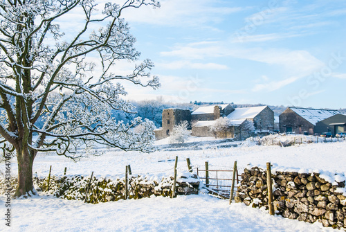 Fotografering Beetham Hall on a snowey Winters day with dry stone wall and gate in foreground
