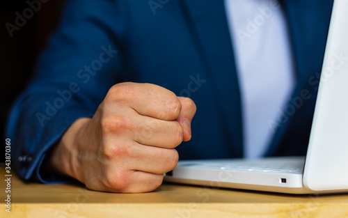 Photographie Close-up of the hands of a well-dressed man in a blue suit and a white shirt hitting the table