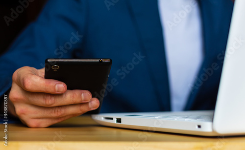 Close-up of the hands of a well-dressed man in a blue suit and a white shirt looking at his smartphone, using a laptop on a desk Poster Mural XXL