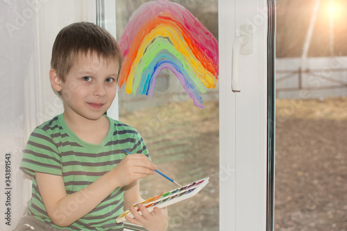 Fotomural The boy painted a rainbow on the window
