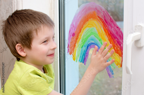 Fotografía Smiling boy painted a rainbow on the window with paint