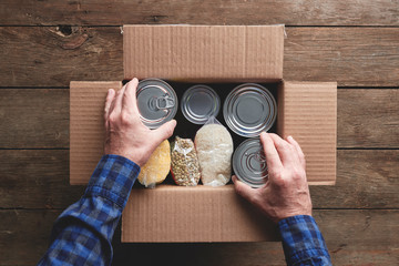 a person packing a donation box with food items