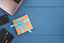 Fathers Day, Birthday And Holiday Concept. Gift Box, Laptop, Smartphone And Note Pad On Blue Wooden Table. Top View, Flat Lay, Copy Space
