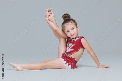 Flexible little girl in beautiful red dress is stretching doing gymnastic exerci Canvas-taulu