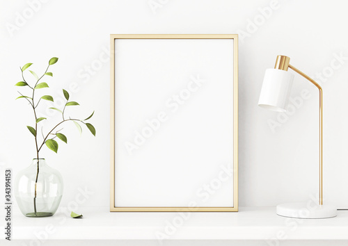 Photo Interior poster mockup with vertical gold metal frame on the shelf with green tree branch in vase and desk lamp on empty white wall background