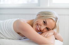 Portrait Of Young Woman With Toothy Smiling On Massage Table